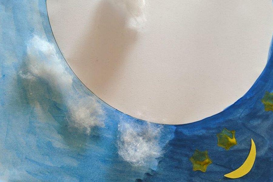 Wolken aus Watte auf einem blau bemalten Papier mit Mond und Sternen