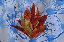 Organge und rote Transparentpapierstücke auf mit blauer Wasserfarbe besprenkeltem Papier