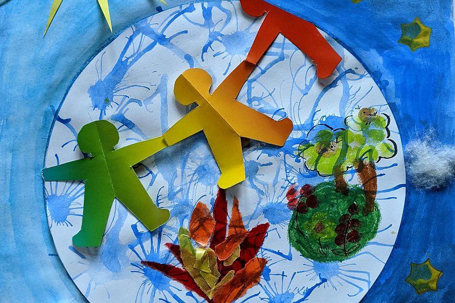 Menschenkette aus buntem Papier auf Bild mit Wasser, Feuer, Blumen und Bäumen