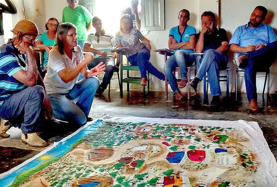 Maria Oberhofer mit auf Tuch gemaltem Schaubild in Menschengruppe