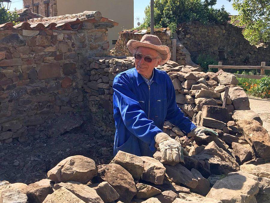 Pater Pius Mühlbacher im Garten bei Arbeiten an einer Steinmauer