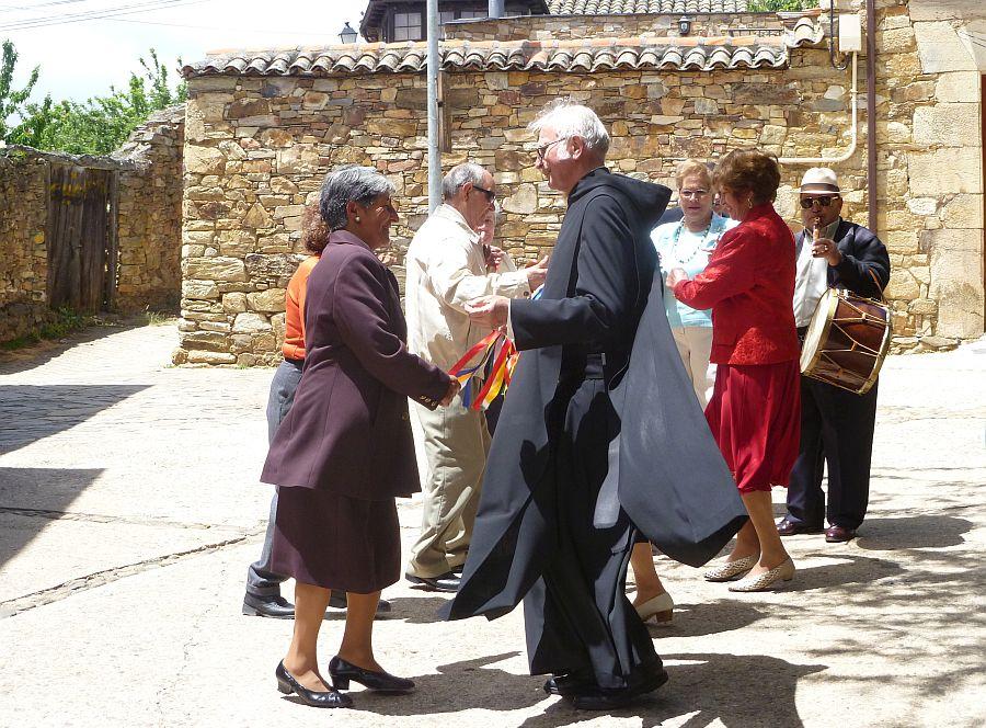Pater Pius tanzt auf Platz mit Dorfbewohnern