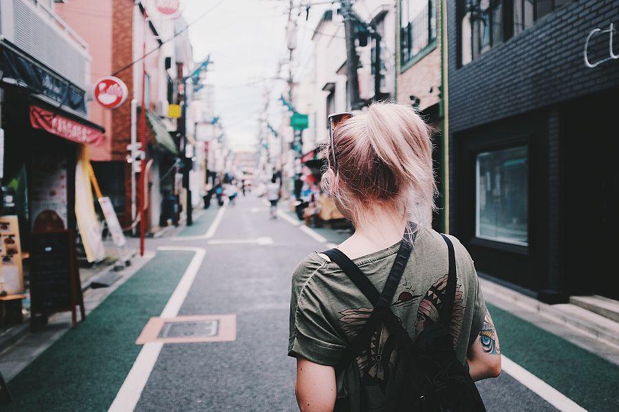 Frau von hinten geht durch Straße in Stadt