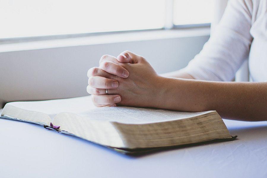 gefaltete Hände auf Buch