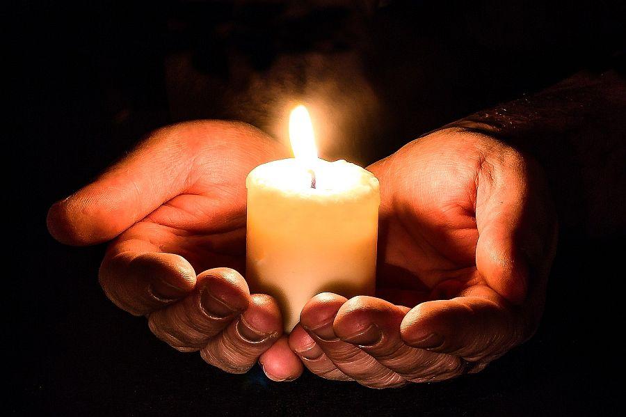 Hände umfassen brennende Kerze