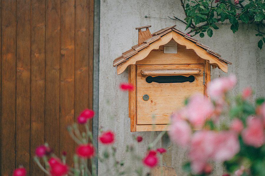 Hölzerner Briefkasten vor Haus mit Blumen