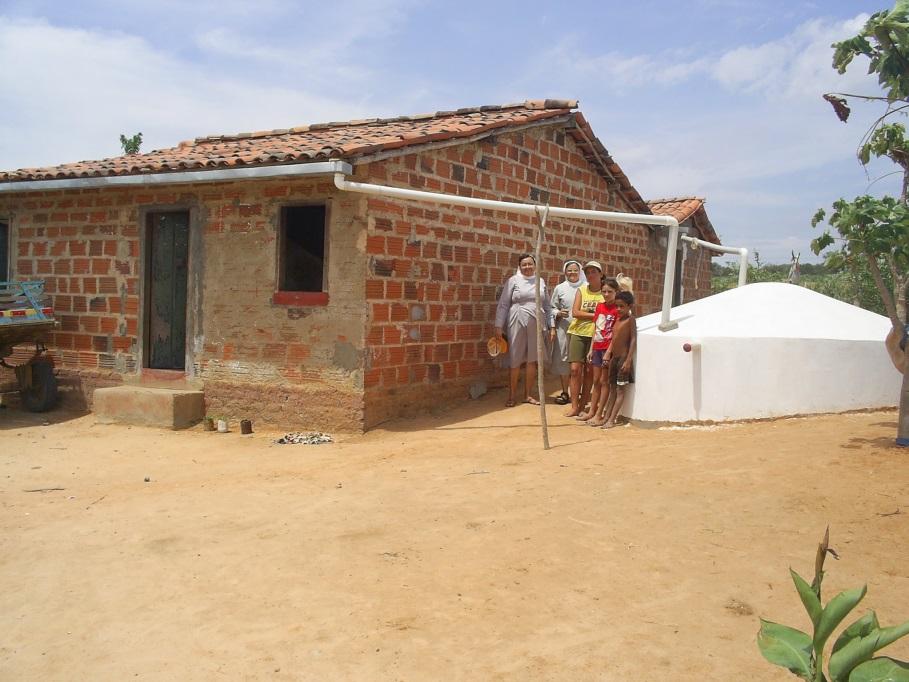 Haus aus Ziegel mit einer Gruppe Erwachsener davor