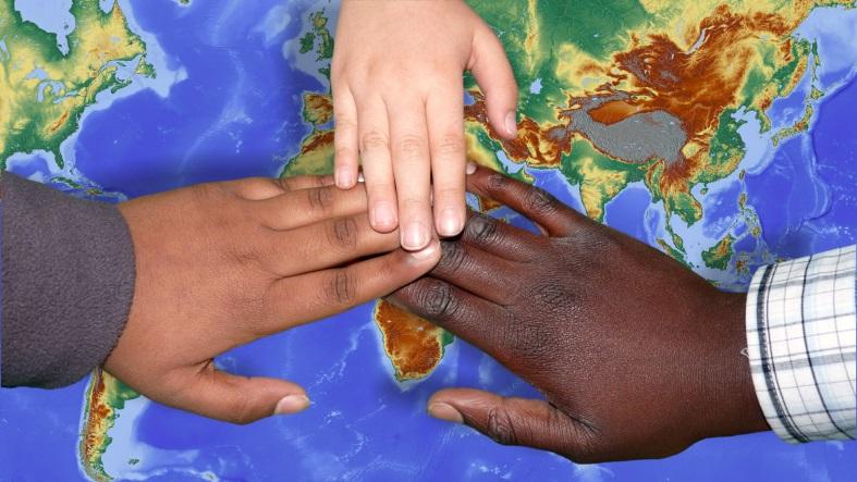 drei verschiedenfarbige Hände über der Weltkarte