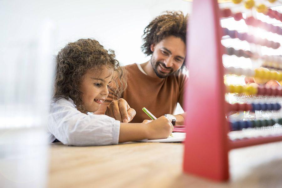Vater fröhlich mit Tochter bei den Hausaufgaben