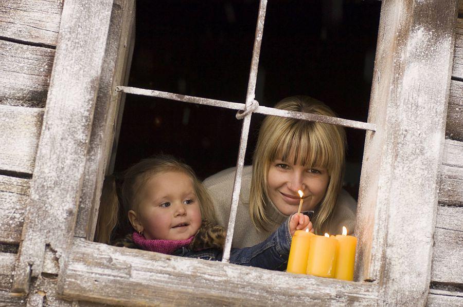 Mutter und Tochter zünden Kerzen an Fenster an