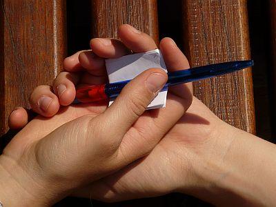 Hände halten Zettel und Stift
