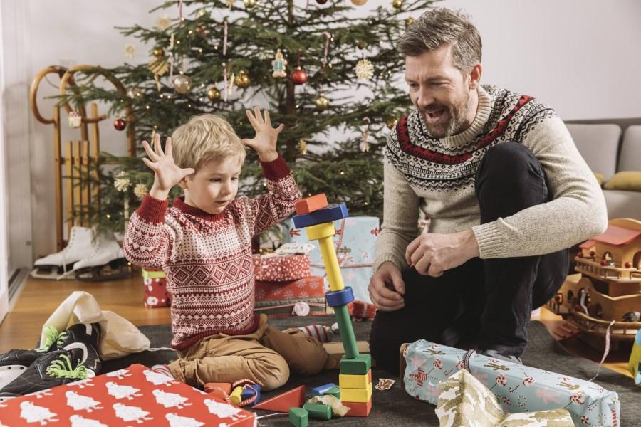 Vater spielt mit Sohn am Weihnachtsbaum
