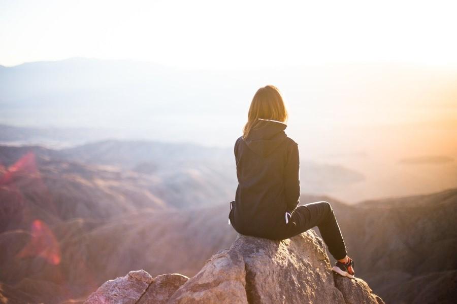 Frau sitzt vor Bergpanorama, allein