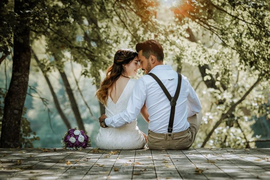 Hochzeitspaare sitzend auf einem Steg