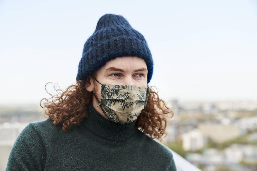 junger Mann nachdenklich mit Maske
