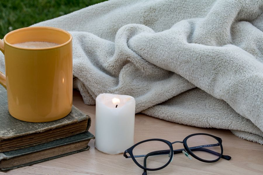 Kerze, Tasse, Bücher und Brille neben Decke