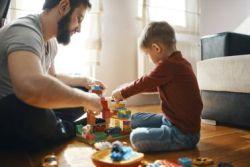vater und sohn spielen mit Lego im wohnzimmer