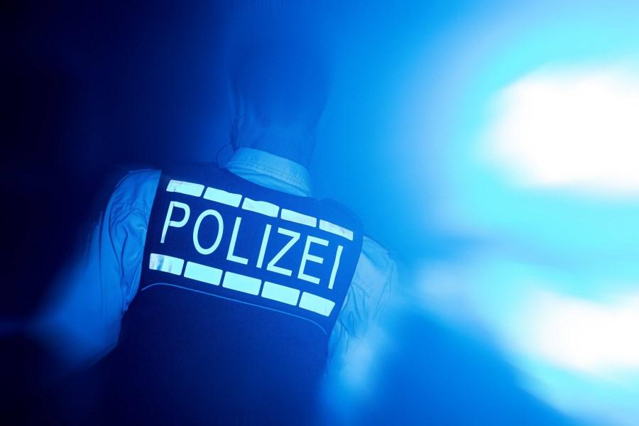 Polizist mit Schutzweste im Dunkeln bei Blaulicht