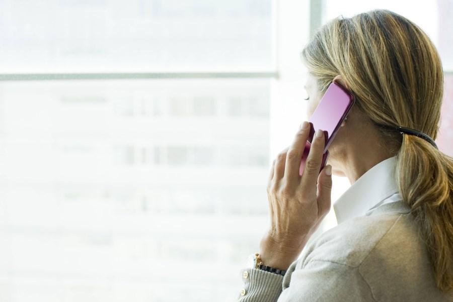 Frau telefoniert mit Handy und blickt aus Fenster