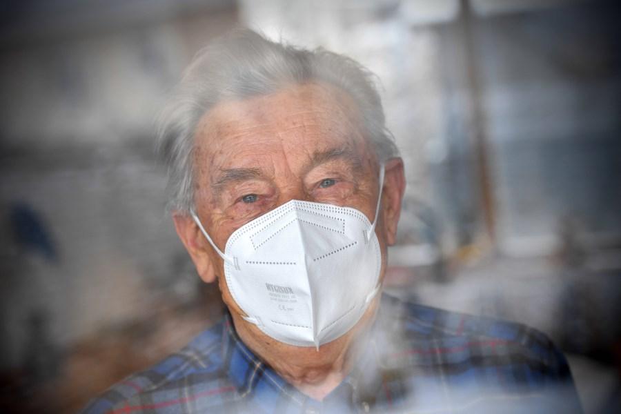älterer Mann hinter Glasscheibe mit Mundnasebedeckung