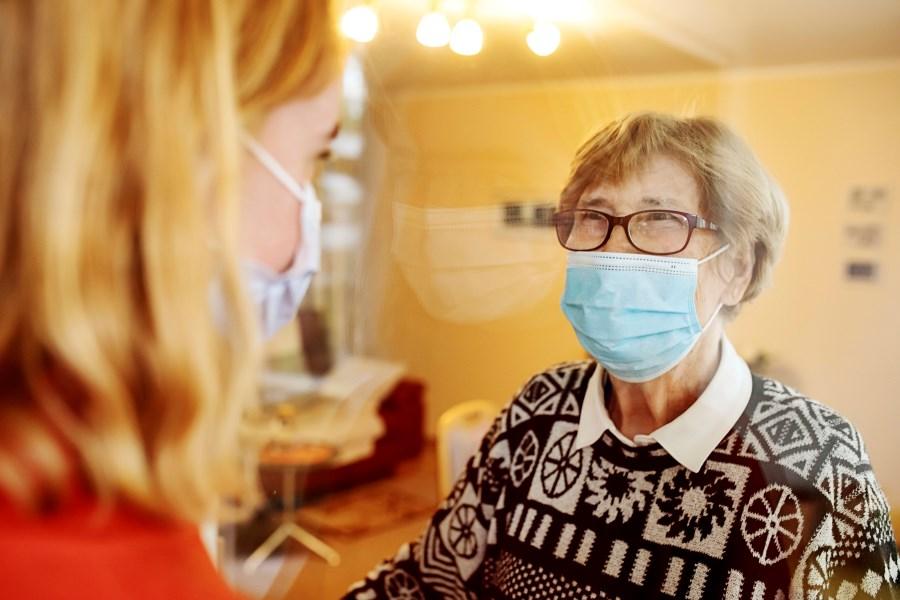 Seniorin und junge Frau unterhalten sich freundlich mit Mundnasebedeckung