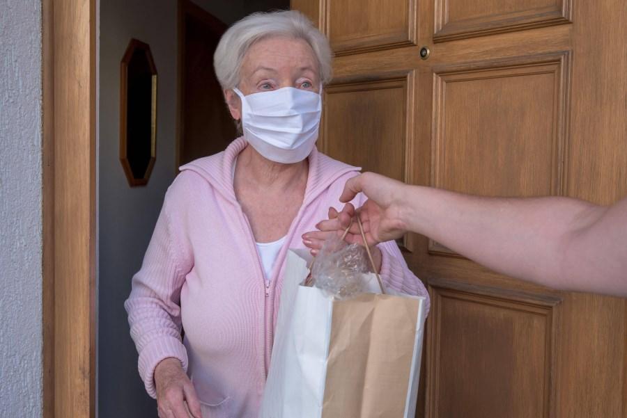 Seniorin übernimmt Einkaufstüte an Haustür mit Mundnasebedeckung