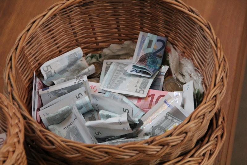 Kollekten-Körbchen mit Geldscheinen und -münzen