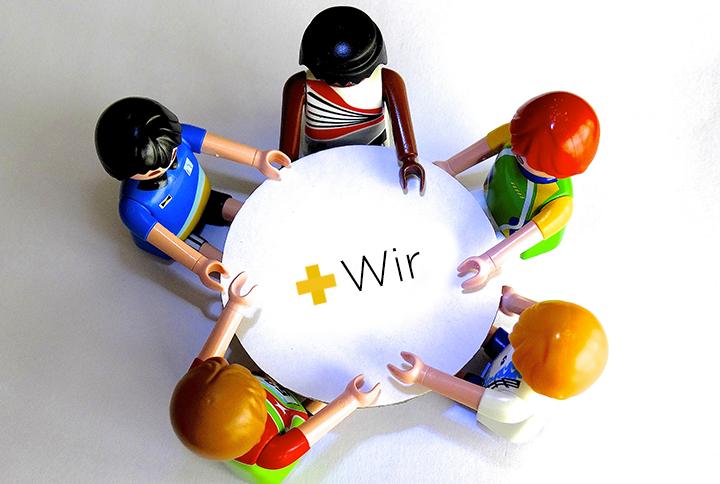 Playmobilfiguren um runden Tisch, Aufschrift Wir