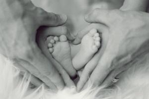 Babyfüße umfasst von zwei Handpaaren in Herzform