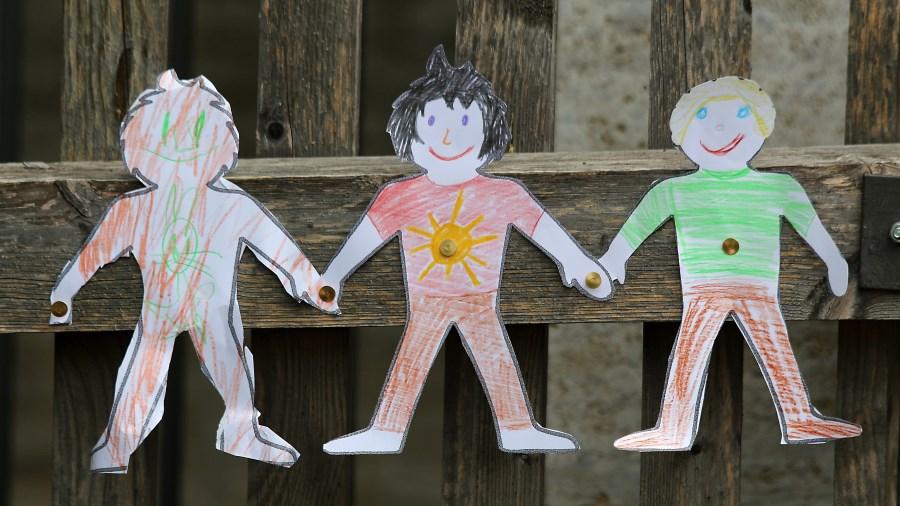Bemalte Kinderfiguren an einem Zaun