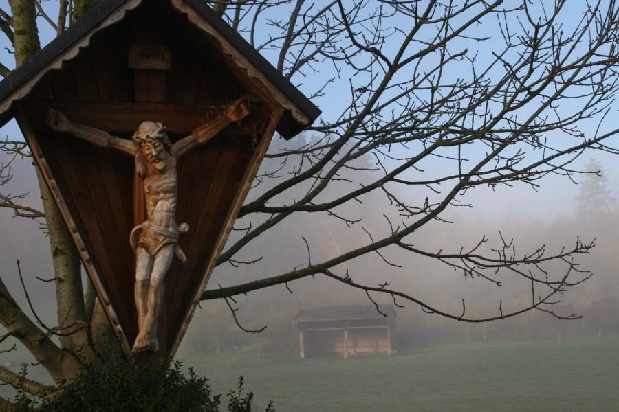 geschnitzes Holzkruzifix in einer nebeligen Herbstlandschaft