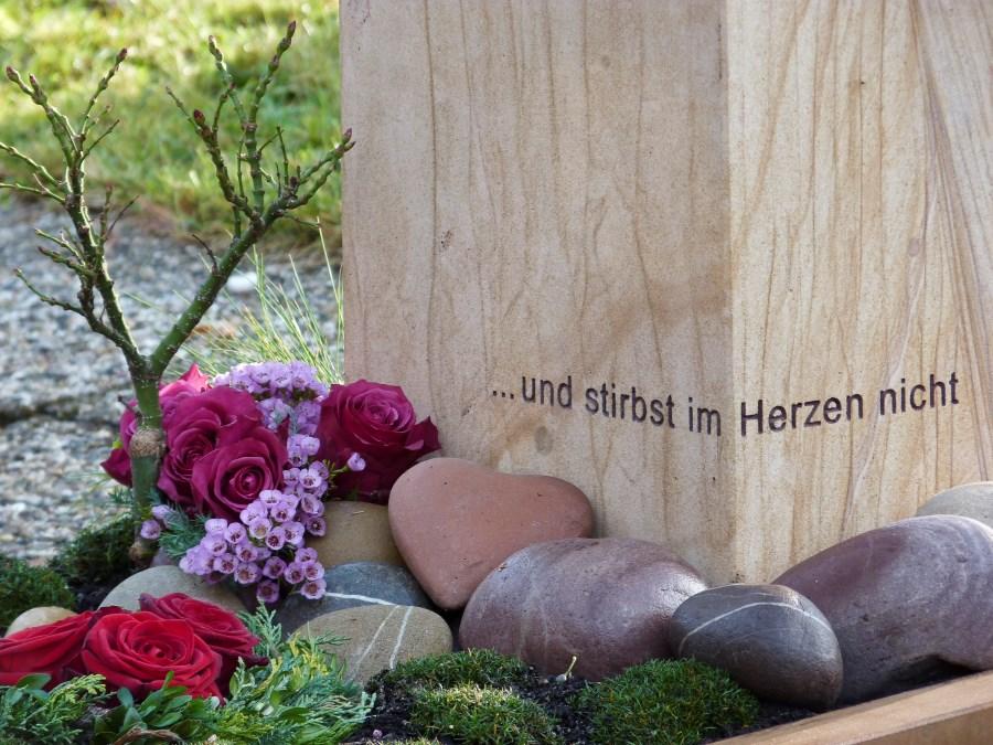 """Grabstein mit der Inschrift """"...und stirbt im Herzen nicht"""" mit Steinen und Blumen davor"""