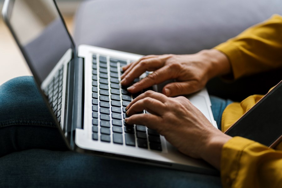 Hände tippen in Laptop auf dem Schoß