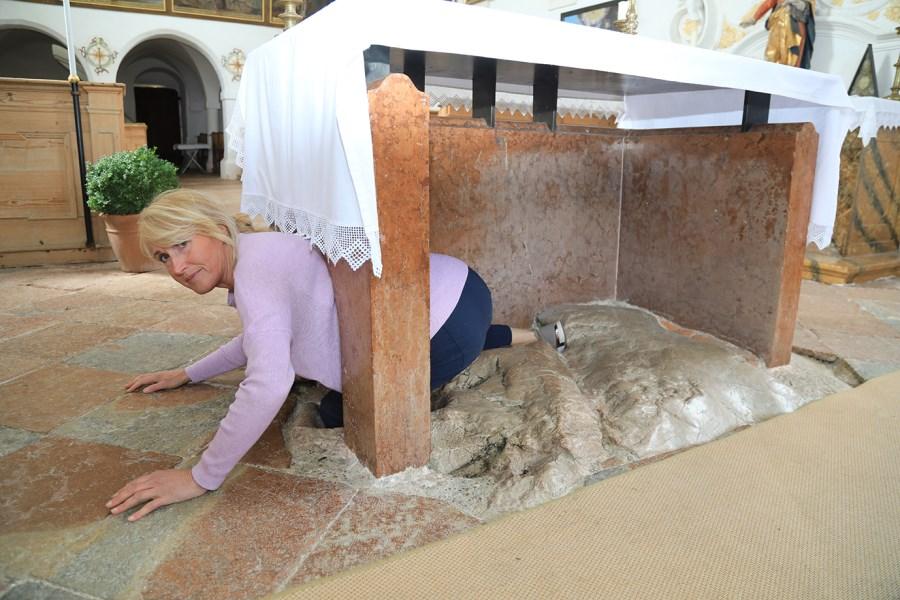 Mesnerin Barbara Schleifer zeigt, wie man seine Füße in die Vertiefungen des Findlings stecken muss, um sich durch das enge marmorne marmorne Schlupfloch zu zwängen