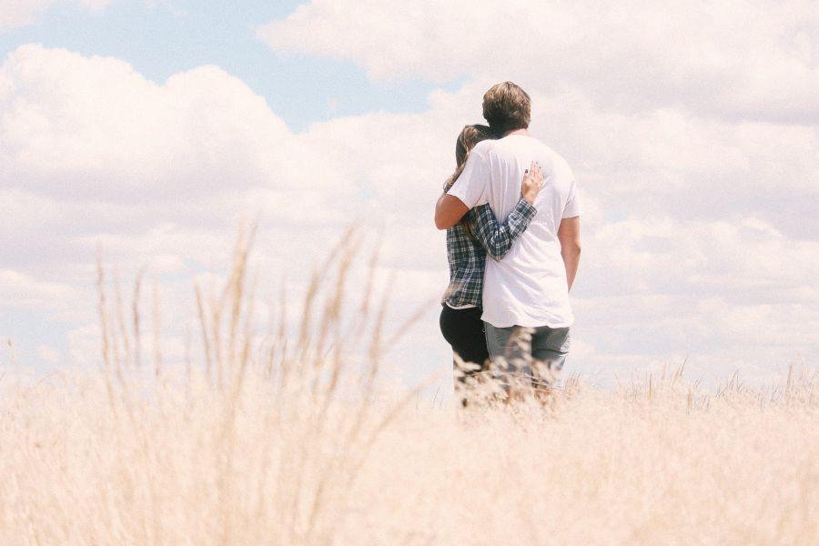 Paar in Feld vor Himmel