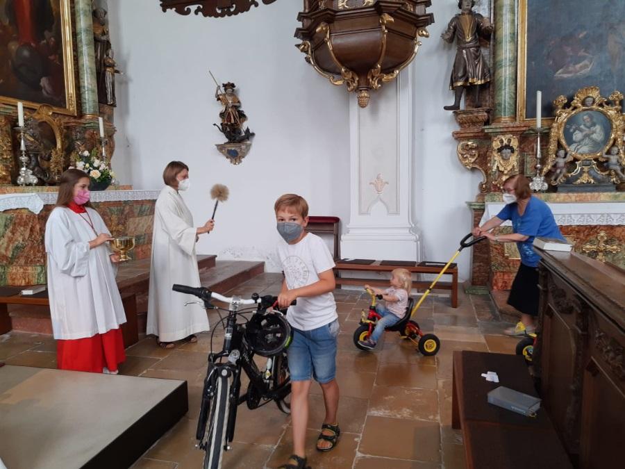 Junge, der Fahrrad schiebt und Mädchen auf Dreirad werden von Seelsorgerin mit Weihwasser gesegnet; Ministrantin assistiert