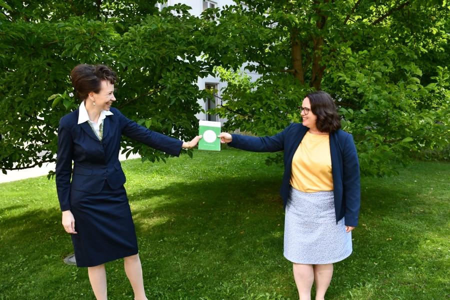 Auf dem Foto sind zwei Frauen zu sehen. Dr. Sandra Krump übergibt  Gabriele Bognitschar ein