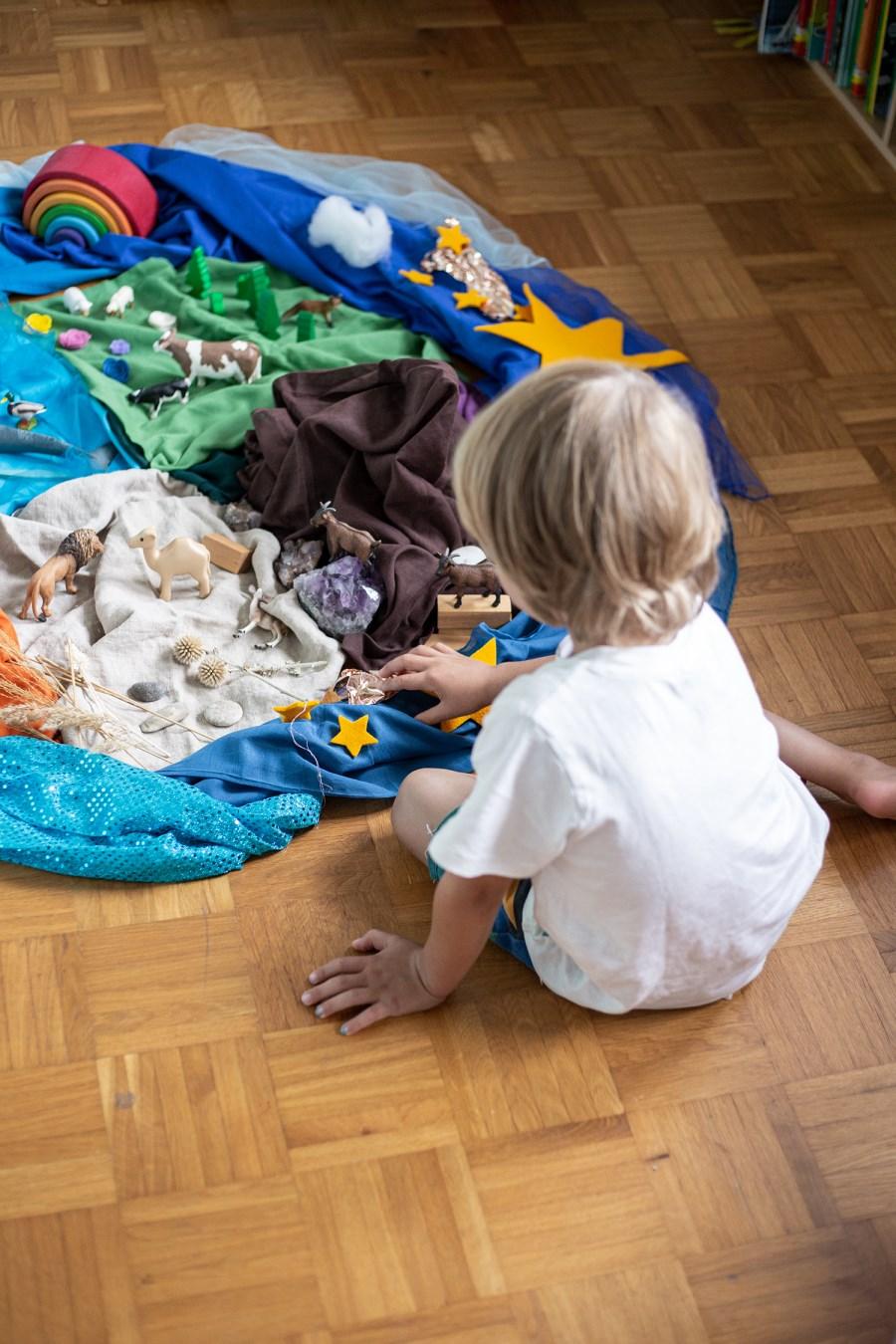 Kind im Kita-Alter spielt mit Bodenbild zum Thema Schöpfung
