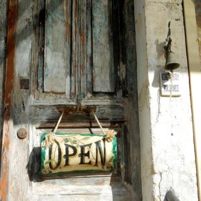 Eine Türe, an der ein Schild mit der Aufschrift OPEN hängt