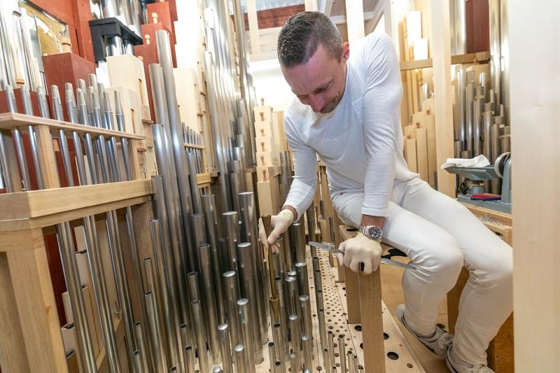 Auf dem Foto ist ein Experte zu sehen, der die Orgel einbaut.
