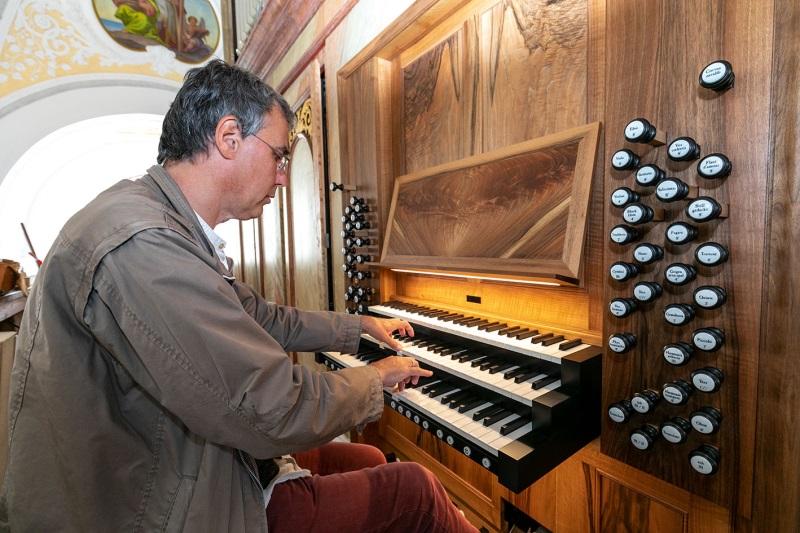 Kirchenmusiker Manfred Müller am Spieltisch der neugebauten Hauptorgel des Papst-Benedikt-Orgelwerks in der Stadtpfarrkirche St. Oswald mit Klaviaturen und Registerzügen.